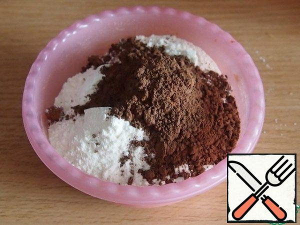 In proteins one by one add the egg yolks and sunflower oil without smell. Sift flour with baking powder and cocoa. Mix, if the dough is very thick, add one or two tablespoons of milk.