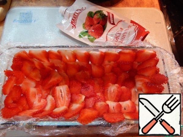 Form with a volume of approximately 1 liter cling film and on the wall place the strawberries (cut into plates) overlap.