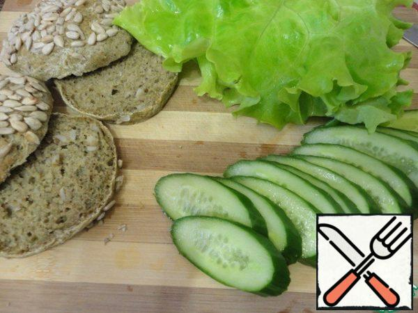 Wash the cucumber and lettuce, dry. Cucumber cut into. Buns cut in half.