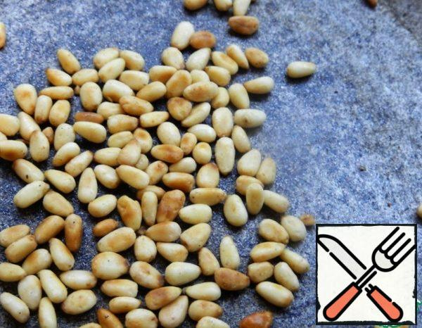 Meanwhile, take the pine nuts and fry them in a dry pan until a pleasant aroma.