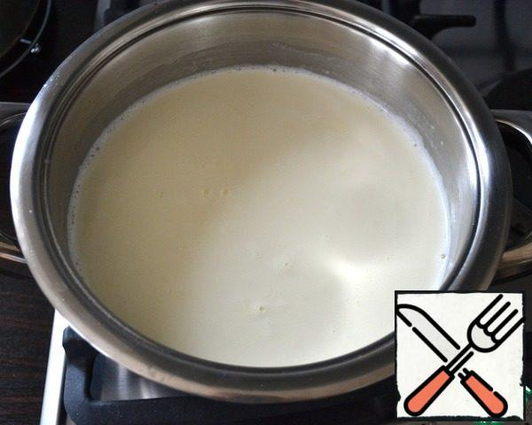 Milk and cream pour into the pan, add vanilla extract, a pinch of salt (optional) and bring the mixture almost to a boil, then reduce the heat to low.