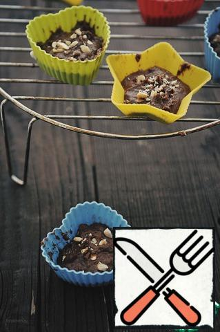 Fry  the nuts in a dry pan and chop coarsely. Molds for cupcakes fill with dough, sprinkle with chopped nuts. Bake at 180*C for about 25 minutes. Cool on the grill and remove from the molds.