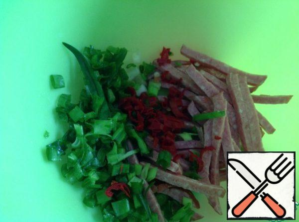 Onions chop, sausage cut into thin cubes. Peel the pepper from the seeds and chop finely.