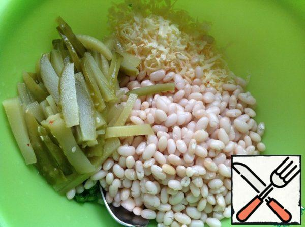 Add boiled beans. Cheese grate on a medium grater, cucumbers cut into strips.