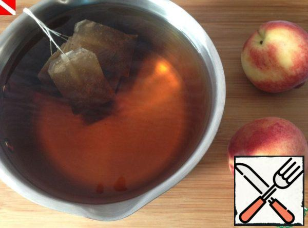 Boil 6 glasses of water, put tea bags in hot water. Let it brew to the desired color and taste. Bags to remove the tea to cool. Before serving, mix tea and peach syrup, add the leaves and berries of black currant.