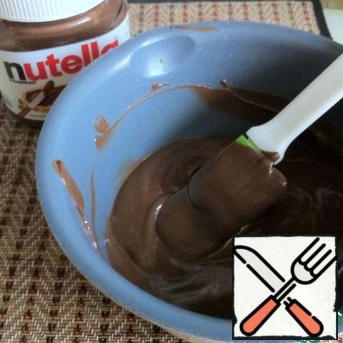 Melt Nutella in a microwave or on a stove, at intervals of 15 seconds. Each time it needs to be mixed with a spatula. The melted Nutella becomes fluid.