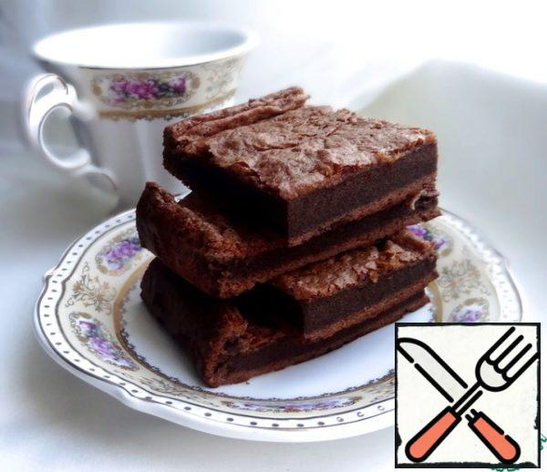 Bake at 180 degrees until dry matches, it took me 25 minutes. The surface of the finished brownies grabs a thin crust. During baking the product rises, and the cooling time will settle. That's OK. Allow to cool in the form, then cut into portions. Bon appetit!