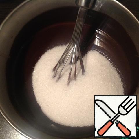Add sugar, salt, vanilla sugar to the cooled chocolate and beat until sugar dissolves. Beat eggs, add to the chocolate mass, mix.