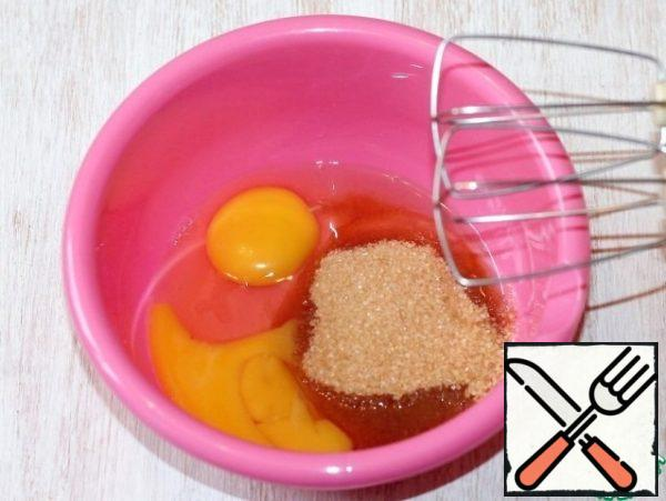 Prepare the chocolate dough. Two large eggs mix with 50 g of sugar and beat with a mixer.