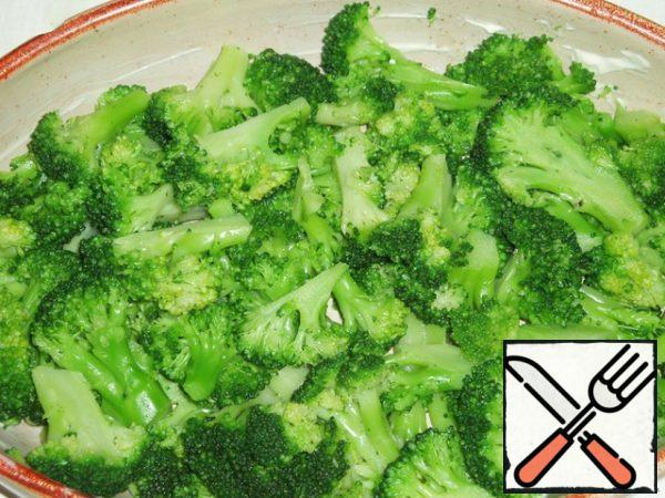 Ready broccoli disassembled into smaller inflorescences, spread in a baking dish, greased with butter.