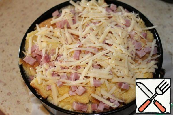 Form lay parchment, grease 1 tbsp. l. vegetable oil, put the contents of the package, tamp hand. Sprinkle the remaining cheese and diced ham on top. Bake in a preheated 190 degree oven for 20-30 minutes, until Browning.