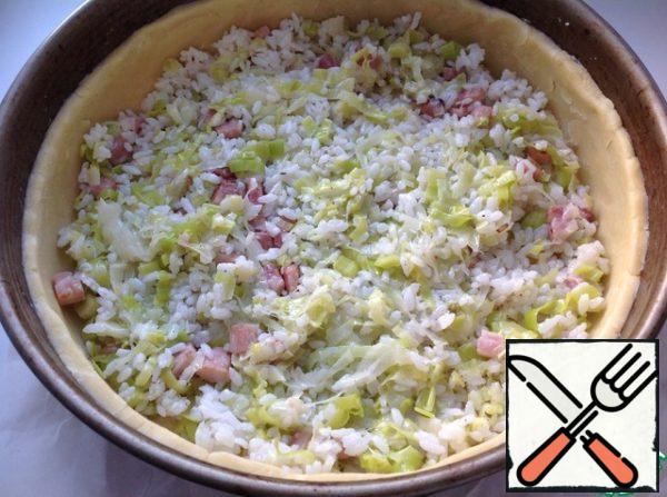 On the dough spread evenly the mixture of rice, onions and bacon.