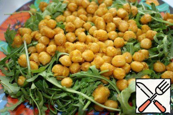 On a platter lay the arugula, then roasted and slightly cooled chickpeas.