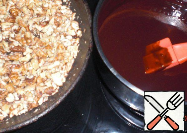 Coarsely chop the nuts and fry in a frying pan. Melt the chocolate with butter.