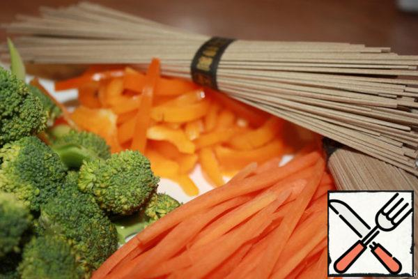 While the meat is marinating, prepare the vegetables. Cut the carrot into strips. Pepper and broccoli strips.