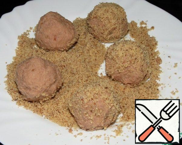 From the resulting mass to roll balls the size of a walnut and roll in crushed nuts.