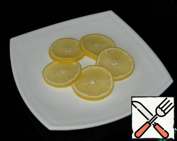 Lemon cut into discs and put on a dish.