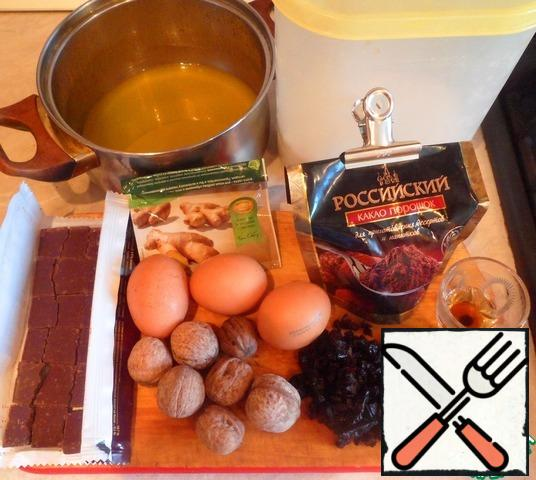 Prepare food for the brownies. Melt the butter, add there to dissolve the broken chocolate, sugar,cocoa, chopped nuts, prunes. Gently kneading, add one egg, add at the end of cognac and ginger. Mix the baking powder with flour and add to our mixture. All carefully stir the mixture with a fork.