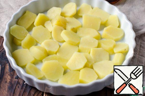 Peel and boil the potatoes, cut into slices and boil in salted water for 5-7 minutes. Put the potatoes in a heat-resistant form, oiled.