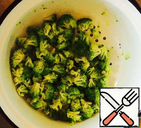 We're not cooking broccoli. We just sort it into medium-sized inflorescences, throw it in a colander and dip it in boiling water. The color of the cabbage will be transformed immediately: it will become emerald! Let's drain all the liquid.