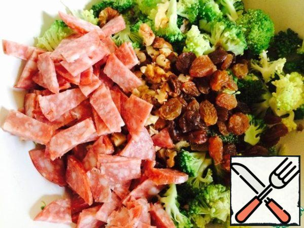 In a bowl put broccoli, walnuts, raisins and sliced into thin small pieces of salami.