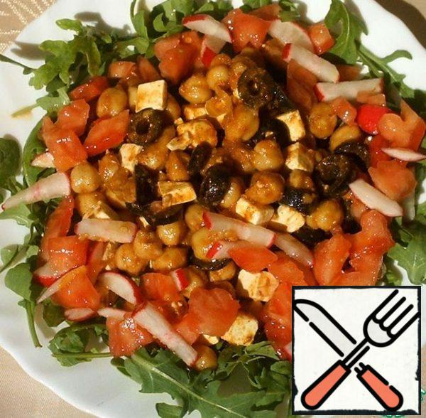 Arugula put on a dish, salt, pepper and put on top of chickpeas. Around to distribute the sauce, radishes and tomato.