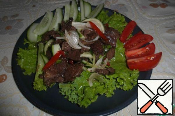The remaining tomato and half cucumber cut into slices. Spread the lettuce on plates, top of lamb with vegetables, pour the sauce remaining in the bowl, decorate with slices of fresh vegetables.