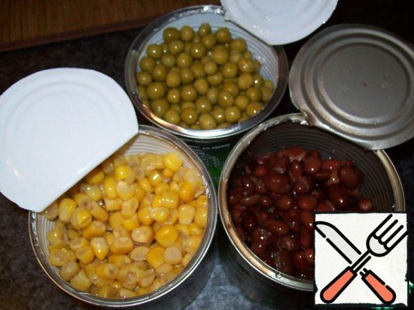 Opened tins of beans, peas and corn, poured the liquid, poured the contents into the bowl.