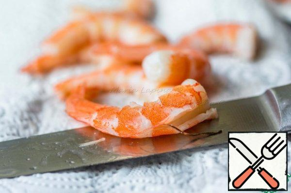 Shrimps clean from the shell, make an incision on the back and remove the dark streak. Cut the shrimp into cubes.
