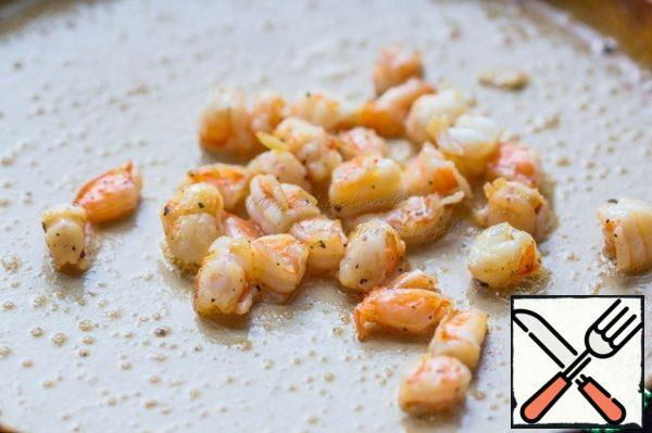In a frying pan, dissolve the butter and fry the shrimp for 2-3 minutes. Salt and pepper.