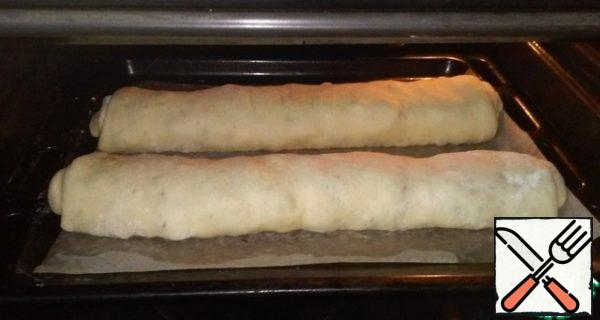 Cover the baking sheet with baking paper and spread the rolls on it. Heat the oven to 180 degrees and send it to the future strudel for 30 minutes. The readiness of the dish can be easily determined by the formation of a Golden brown crust. Grease the top with a piece of butter.