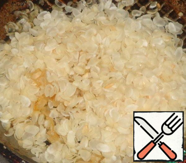To the onions add the rice flakes and mix well.