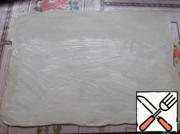 Roll out very thin dough. I have a silicone Mat, but you can use a towel, well sprinkle it with flour (if the dough is rolled out just on the table, then it will be very difficult to fold the strudel and transfer it to the baking sheet). Softened with butter (about 20-30 g), grease the dough layer, except for about 10 cm from one edge (this will be the seam).