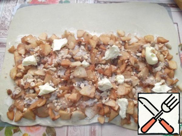 Lay out evenly apples, raisins, nuts, sprinkle with sugar and cinnamon and distribute the rest of the butter.