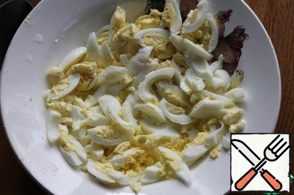 Boil eggs, peel and cut into strips. Also chop arugula. In a bowl, mix the sour cream with finely chopped garlic, salt and pepper.