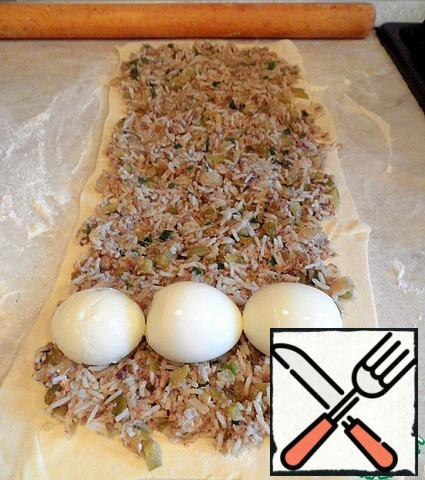 Roll out the dough with a rolling pin and put the filling. Peel the boiled eggs, and put in a row.