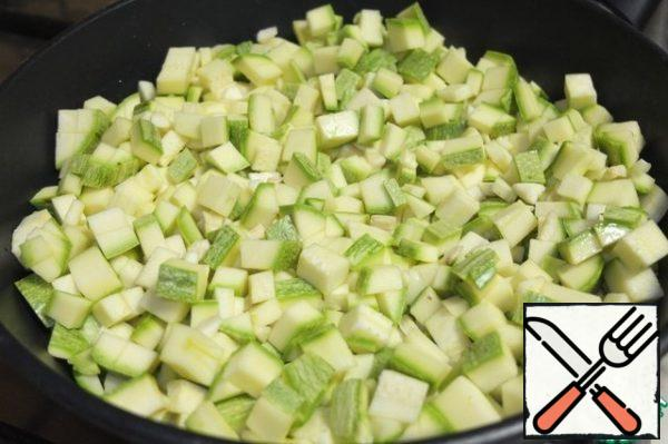 Add, cut into small cubes zucchini and finely chopped garlic.