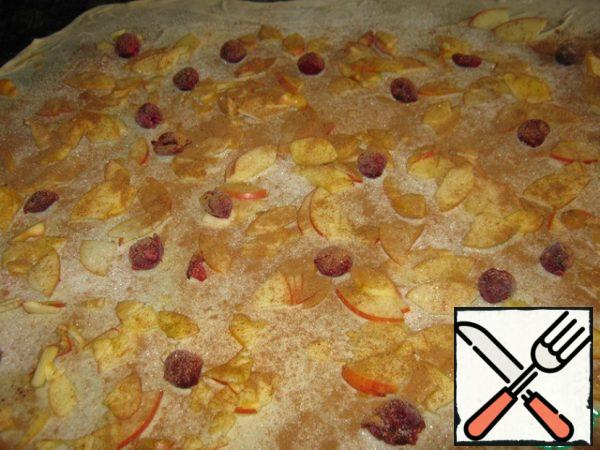 On the resulting layer of the test, apply a brush rust. oil (not a solid layer, and strokes), sprinkle of breadcrumbs, evenly distribute apples, cherries, sprinkle with cinnamon, 4 tbsp sugar and vanilla.