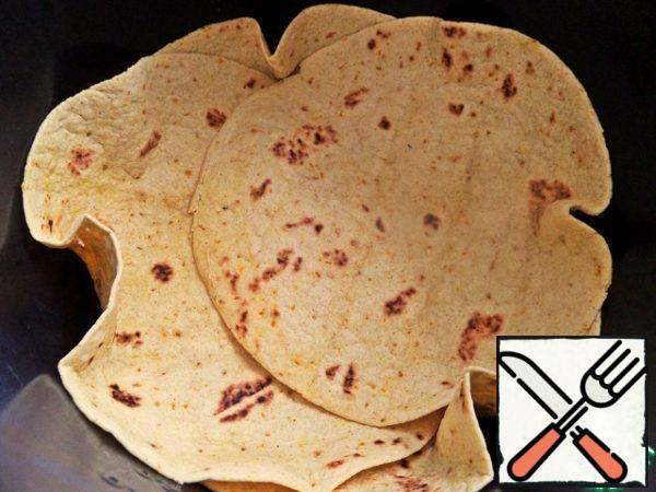 Thoroughly grease the slow cooker at the bottom of the bowl and put the tortillas overlap.
