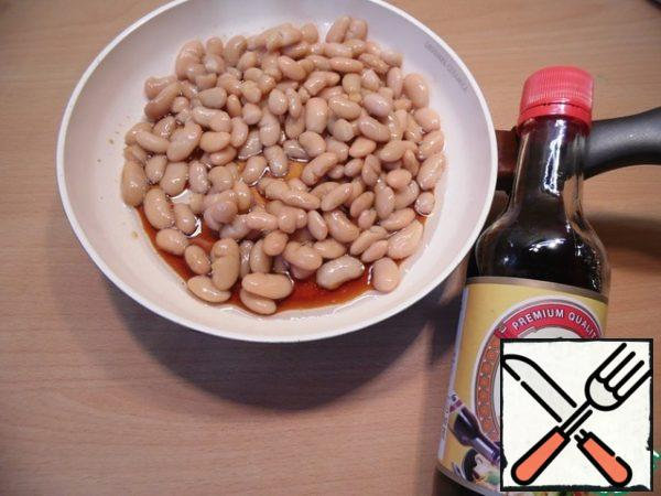 From the beans to drain off the liquid, chop the garlic, put into a frying pan greased with vegetable oil, add soy sauce and wine vinegar and simmer, stirring occasionally, until the liquid is evaporated. The beans are cool, slightly mash.