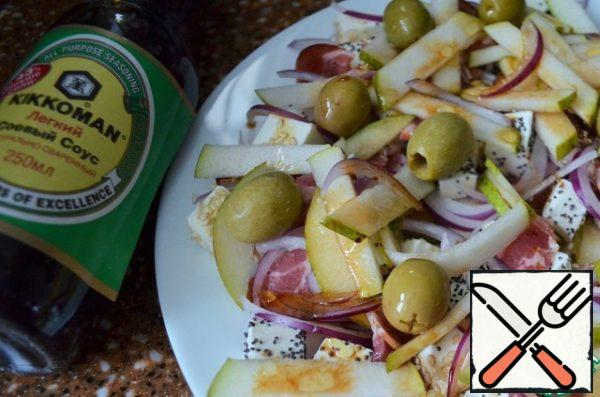 Peel the onion, cut it with feathers and put it on a dish. The remaining part of the pear cut into thin strips, spread on top with olives.