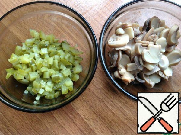 Cut cucumbers into small cubes. With mushrooms drain off any excess liquid. If they are large, then cut them into small pieces.
