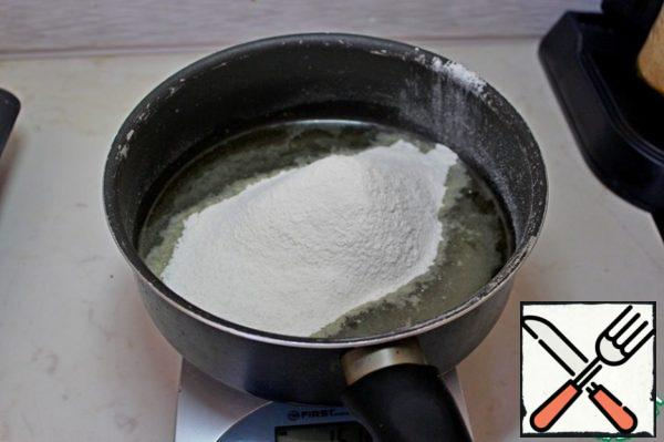 Let's start with the preparation of dough for profiteroles. To do this, pour water and vegetable oil into a saucepan, bring to a boil and without removing from heat with constant stirring pour the sifted flour.