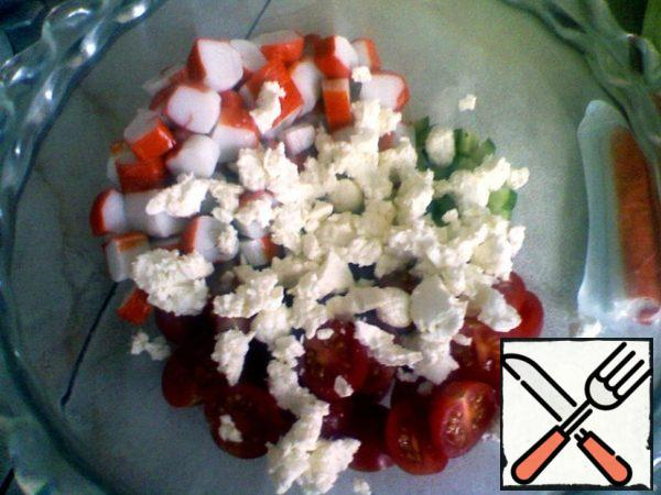 Crab sticks cut into rings. Cut the cucumber into small cubes. Cut tomatoes in half. Salad to break it. Cheese roll into small balls.