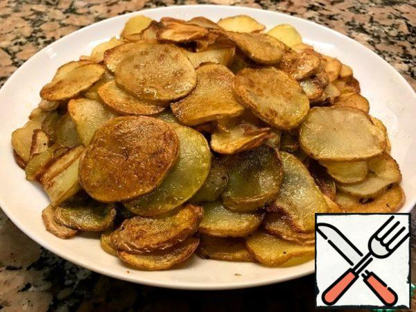 Cut the potatoes into thin plates and fry in olive oil until Golden brown.