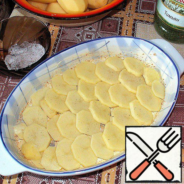 Cover the bottom of the form with a layer of potatoes, which sprinkle with a mixture of salt and spices.