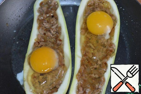 Zucchini boats with salt, fill halfway with stuffing. In a frying pan pour the broth, put the stuffed zucchini, in each half gently break one egg, salt. Cover and put on fire. Cook approx 10 min, the Protein must be prepared, and the yolk is better to leave the liquid.