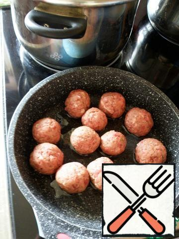 Drop the rice into the water. Roll the meatballs and fry them quickly from all sides.