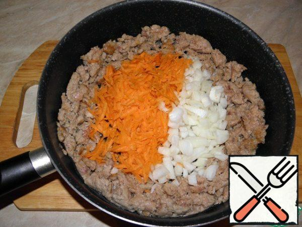 Push the minced meat to the walls of the pan and add chopped onions and grated carrots to the center. Lightly fry the vegetables in the center of the dishes.