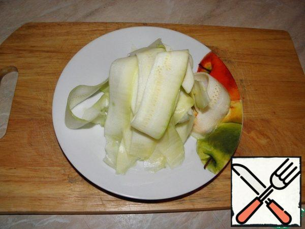 While the vegetables with minced meat cooked in a pan, prepare the zucchini. Wash, dry, peel. Cut the zucchini along into two parts, remove the seeds from each with a spoon, peeler or knife — to whom it is more convenient, cut the ends. At this stage, just determined by the weight of zucchini. Remove the zucchini pulp layer by layer.
